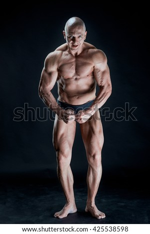 handsome muscular young bodybuilder showing his muscles and abs while posing shirtless.  Isolated on black background