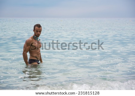 Handsome muscular young man at the beach standing in the sea in profile pose - stock photo