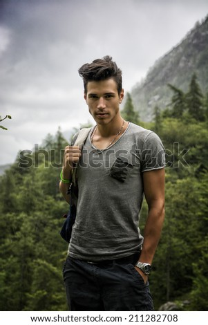 Handsome muscular young man backpacking or hiking in lush green mountain scenery looking at camera