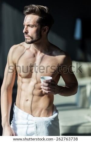 Handsome, muscular, young man drinking tea in a hotel room standing next to a window and looking against bright sunlight with towel wrapped around his waist - stock photo