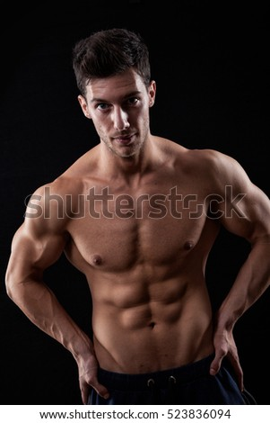 Handsome muscular young man posing over black background.