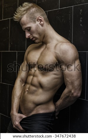 Handsome, muscular young man shirtless leaning against tiled wall, looking at camera - stock photo
