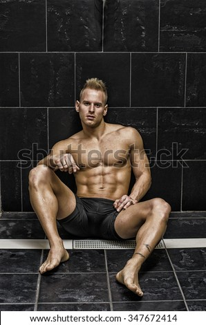 Handsome, muscular young man shirtless sitting against dark tiled wall, looking at camera - stock photo