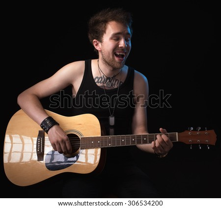 handsome musician playing guitar on black background