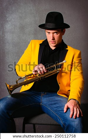 Handsome musician trumpet player with trumpet at studio. Jazz-band. Brutal young musician holding trumpet - stock photo