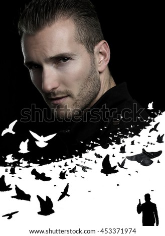 Handsome mysterious man posing over a black background - stock photo