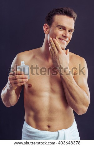 Handsome naked man is smiling, holding aftershave lotion and applying it, on a dark background