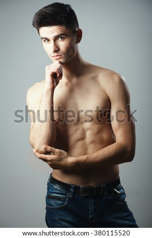 Handsome naked torso young man guy isolated on gray background. Looking at camera.