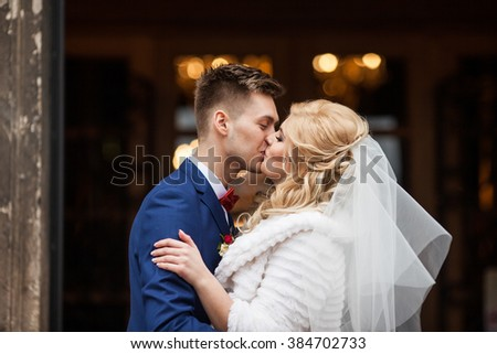 Handsome newlywed groom kissing happy bride outside church after ceremony