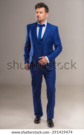 Handsome nifty man in stylish blue suit and tie posing at studio. Full length. - stock photo