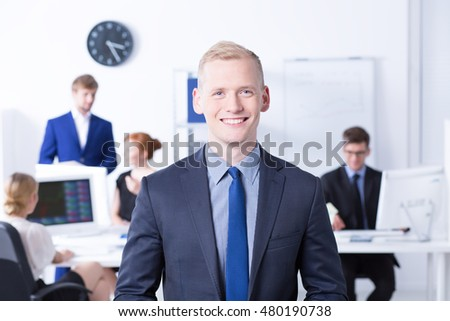 Handsome office worker wearing suit, in the background employess during work