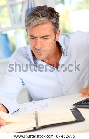Handsome office worker writing notes on agenda