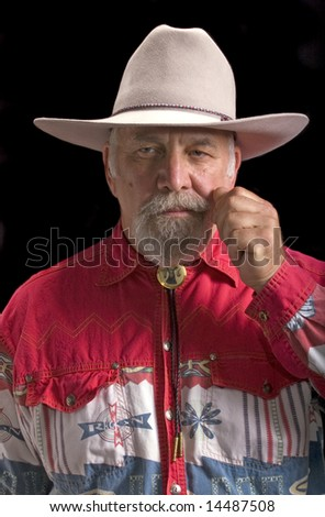 Handsome old baby-boomer Cowboy on black and looking like Buffalo Bill Cody - stock photo