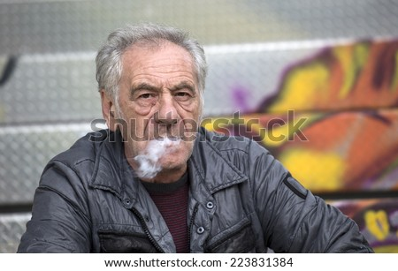 handsome old italian man smoking   - stock photo