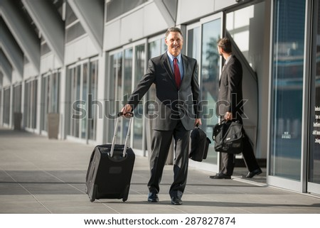 Handsome older businessman with a carry on bag walks through airport outside - stock photo