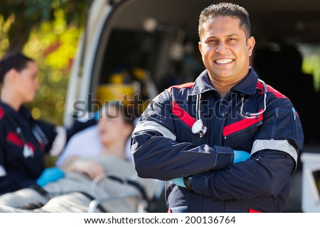 handsome paramedic in front of patient and colleague - stock photo