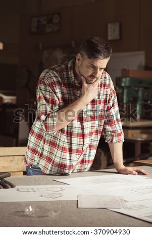 Handsome, pensive carpenter standing over workbench, analysing project