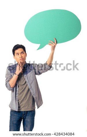 Handsome pensive young Chinese man is holding speech bubble, looking at it and thinking, isolated on white background - stock photo