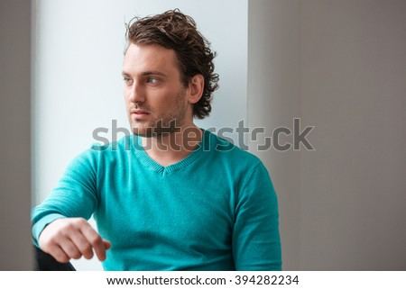 Handsome pensive young man sitting and looking at the window over white background  - stock photo