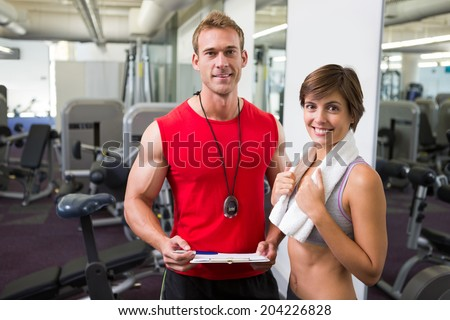 Handsome personal trainer with his client smiling at camera at the gym - stock photo