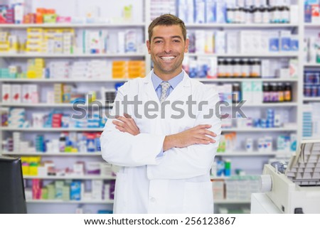 Handsome pharmacist smiling at camera at the hospital pharmacy