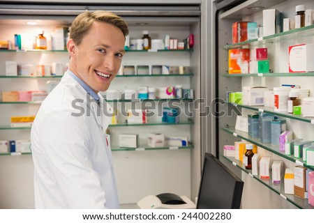 Handsome pharmacist using the computer at the hospital pharmacy