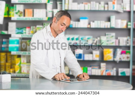 Handsome Pharmacist with Digital Tablet in a Drugstore - stock photo