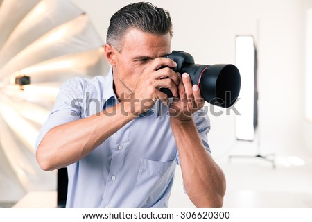 Handsome photographer making photo on camera in studio - stock photo
