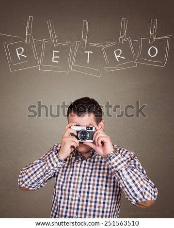 Handsome photographer man taking a picture with old retro (vintage) camera on old brown wall background with  photo frames hanging on a rope held by clothespins design concept  - Retro text - stock photo