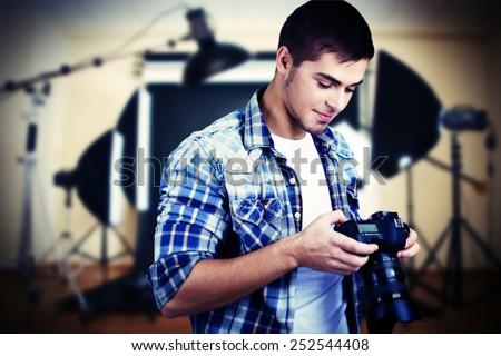 Handsome photographer with camera in photo studio - stock photo