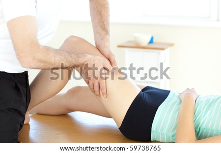Handsome physical therapist giving a leg massage in a health center - stock photo