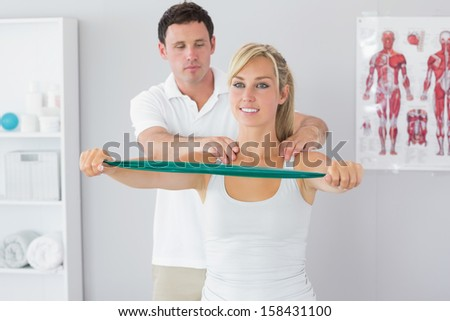 Handsome physiotherapist correcting position of patient in bright office - stock photo
