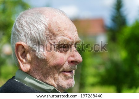 Handsome 80 plus year old senior man posing for a portrait in his garden.  - stock photo
