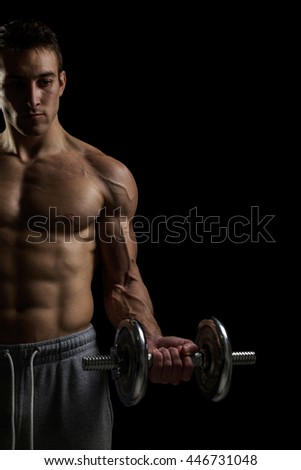 Handsome power athletic man in training pumping up muscles with dumbbell. Isolated over black background - stock photo