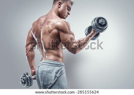 Handsome power athletic man in training pumping up muscles with dumbbell. Strong bodybuilder with six pack, perfect abs, shoulders, biceps, triceps and chest. Image with clipping path - stock photo