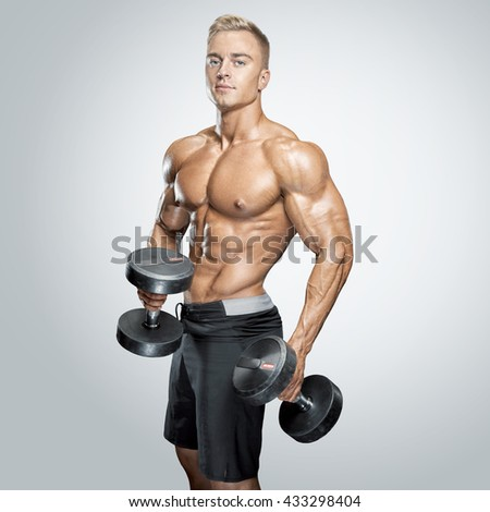 Handsome power athletic man in training pumping up muscles with dumbbells in a gym. Fitness muscular body isolated on white background. - stock photo