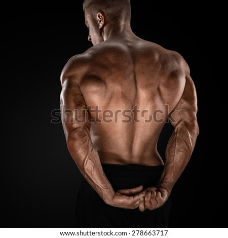 Handsome power athletic man showing his back. Strong bodybuilder with shoulders, biceps, triceps and chest