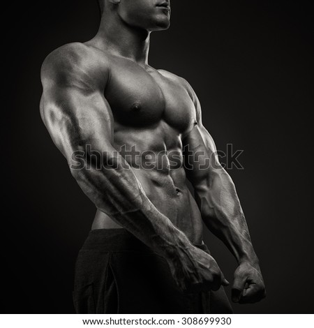Handsome power athletic man with dumbbell confidently looking forward. Strong bodybuilder with six pack, perfect abs, shoulders, biceps, triceps and chest - stock photo