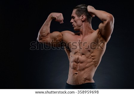 Handsome power athletic young man with great physique. Strong bodybuilder with six pack, perfect abs, shoulders, biceps, triceps and chest. - stock photo
