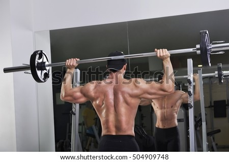Handsome powerful athletic man doing barbell shoulder press exercise. Strong bodybuilder with perfect muscles.