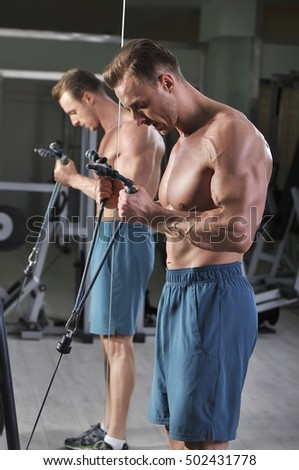 Handsome powerful athletic man doing biceps exercise with cables. Strong bodybuilder with perfect muscles.