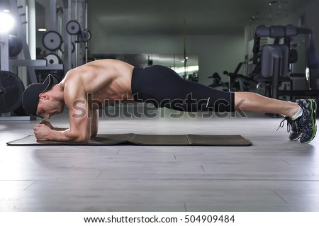 Handsome powerful athletic man doing plank exercise. Strong bodybuilder with  perfect muscular abs, back and arms.