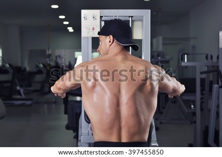 Handsome powerful athletic man performing back exercise. Strong bodybuilder with perfect muscles.