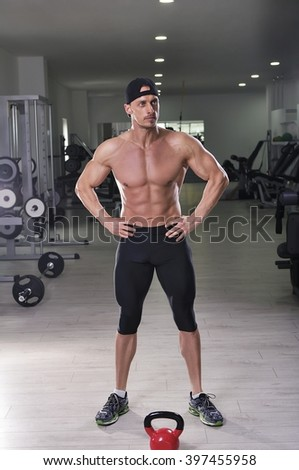 Handsome powerful athletic man posing at the gym. Strong bodybuilder with perfect abs, chest, shoulders, arms and legs. - stock photo