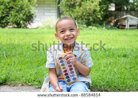 Handsome Preschool Age Little Boy Laughing Looking at Camera holding paint set sitting on front yard lawn during daytime daylight - stock photo
