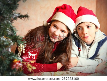 handsome preteen boy and his sister in christmas santa hat and tree