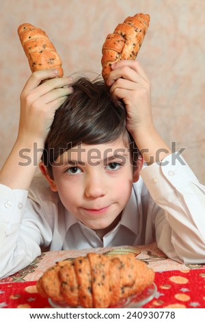 handsome preteen boy play with croissant imagine sail sheep