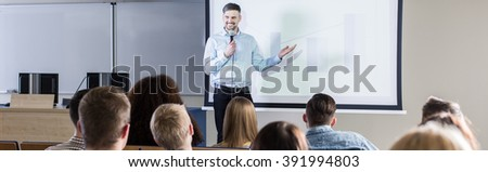 Handsome professor presenting his topic to students during lecture on university