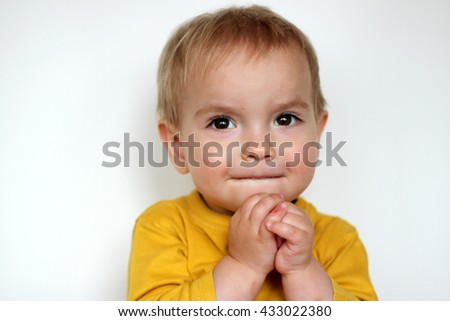 Handsome rapturous small toddler boy in yellow T-shirt smiling sincerely over white background, face emotions concept, indoor close-up - stock photo