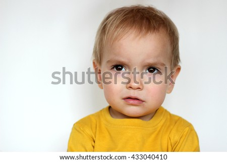 Handsome rapturous small toddler boy in yellow T-shirt with dissatisfied face over white background, face emotions concept, indoor close-up - stock photo